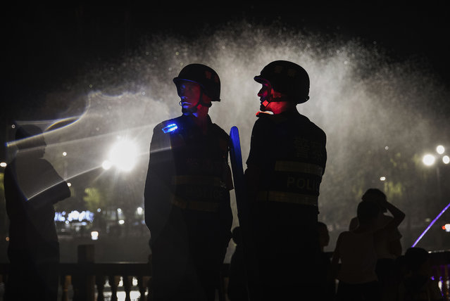 Police officers guard near a new laser and water show that is part of a local government tourism development on June 30, 2017 in the old town of Kashgar, in the far western Xinjiang province, China. (Photo by Kevin Frayer/Getty Images)