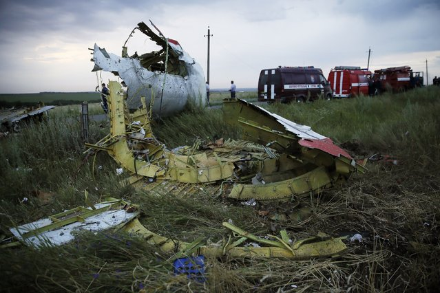 """A picture taken near the town of Shaktarsk, in rebel-held east Ukraine, on July 17, 2014 shows the wreckages of the Malaysian airliner carrying 295 people from Amsterdam to Kuala Lumpur after it crashed. Malaysia Airlines said today it had """"lost contact"""" with one of its passenger planes carrying 295 people over eastern Ukraine, amid speculation it had been shot down. (Photo by Zurab Dzhavakhadze/AFP Photo)"""