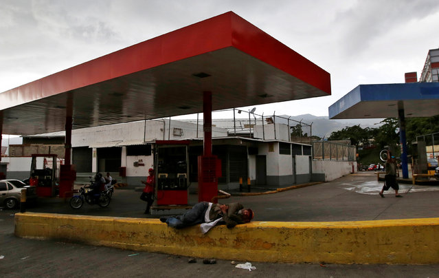 A man rests next to a gas station in Caracas, Venezuela, June 21, 2016. (Photo by Mariana Bazo/Reuters)