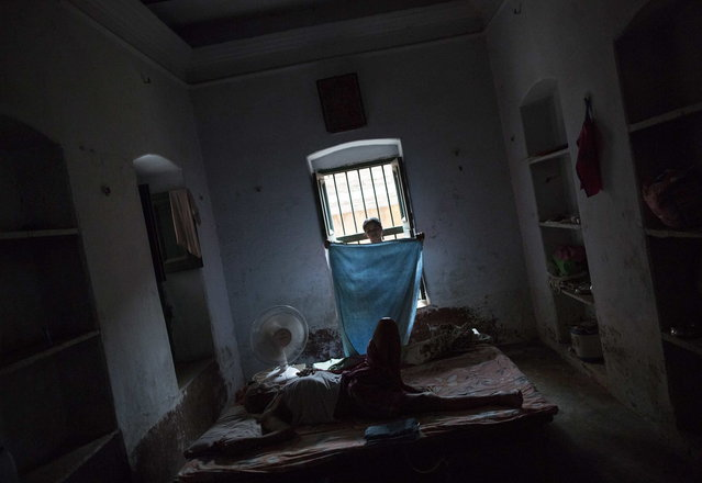Kishore Pandey, 82, lies on a bed as his daughter Neelam Tiwari folds a cloth at Mukti Bhavan (Salvation House) in Varanasi, in the northern Indian state of Uttar Pradesh, June 17, 2014. (Photo by Danish Siddiqui/Reuters)