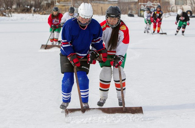 Members of Kyrgyzstan's first female hockey team clean the ice during a training session in the village of Otradnoye, Kyrgyzstan on February 4, 2020. (Photo by Vladimir Pirogov/Reuters)