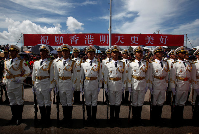"People's Liberation Army naval soldiers stand in front of a banner which reads ""Hope Hong Kong has an even better tomorrow"" at a naval base, celebrating the 19th anniversary of Hong Kong's handover to Chinese sovereignty from British rule, in Hong Kong July 1, 2016. (Photo by Bobby Yip/Reuters)"