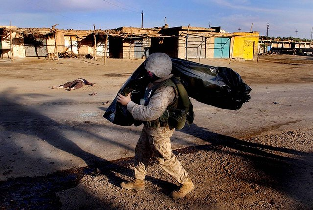 A U.S. Marine carries the body of a fellow Marine killed in action after a coordinated ambush against American troops in Ramadi, April 6, 2004