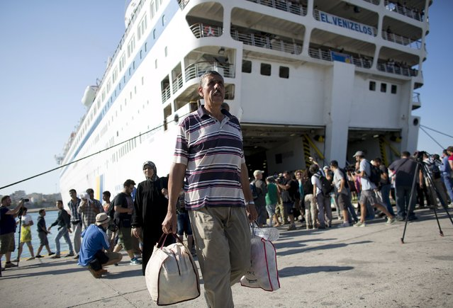 """A Syrian refugee man carries his luggage as he walks out of """"Eleftherios Venizelos"""" passenger ship after its arrival at the port of Piraeus near Athens, Greece, August 20, 2015. (Photo by Stoyan Nenov/Reuters)"""