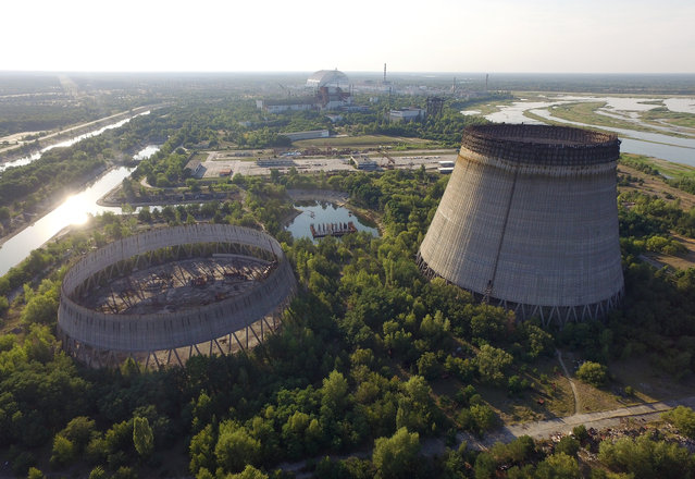 In this aerial view abandoned, partially-completed cooling towers stand at the Chernobyl nuclear power plant as the new, giant enclosure that covers devastated reactor number four stands behind on August 18, 2017 near Chornobyl, Ukraine. (Photo by Sean Gallup/Getty Images)