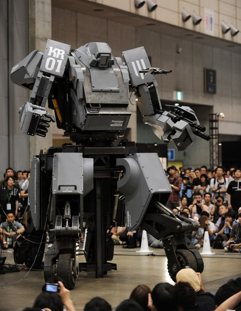 """Japanese electronics company Suidobashi Heavy Industry unveils its latest robot """"Kuratas"""" (C) as a crowd of people take photographs at the Wonder Festival in Chiba, suburban Tokyo on July 29, 2012. The Kuratas robot, which will go on sale with a price tag of one million USD, measures four meters in height, weighs four tons and has four wheeled legs that can either be controlled remotely through the 3G network or by a human seated within the cockpit."""