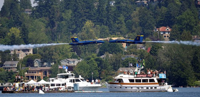 Two U.S. Navy Blue Angels make a narrow pass past each other as they fly over boats on Lake Washington during the Seafair Air Show, Sunday, August 3, 2014, in Seattle. The races are part of Seattle's annual Seafair weekend. (Photo by Ted S. Warren/AP Photo)