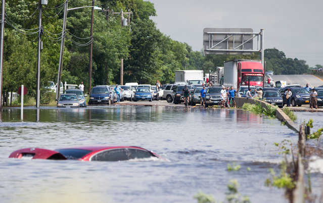 People look on as a car remains flooded on Sunrise Highway at Route 111 following heavy rains and flash flooding August 13, 2014 in Islip, New York. The south shore of Long Island along with the tri-state region saw record setting rain that caused roads to flood entrapping some motorists. (Photo by Andrew Theodorakis/Getty Images)