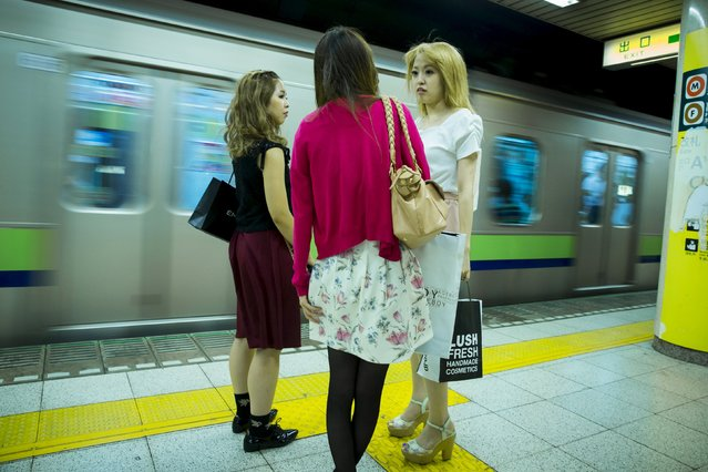 Women stand on the platform as a train pulls into Shinjuku Sanchome station in Tokyo, August 27, 2015. (Photo by Thomas Peter/Reuters)