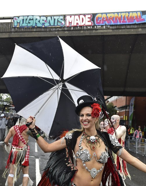 A performer shields herself with an umbrella as she dances at the Notting Hill Carnival in west London, August 31, 2015. (Photo by Toby Melville/Reuters)