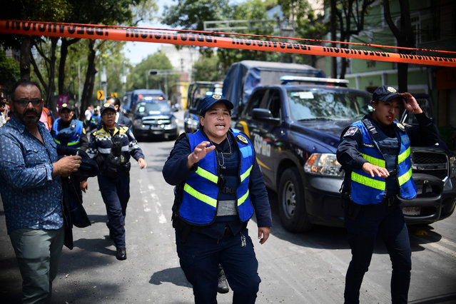 Police officers cordon the area off after a building collapsed during a quake in Mexico City on September 19, 2017. (Photo by Ronaldo Schemidt/AFP Photo)