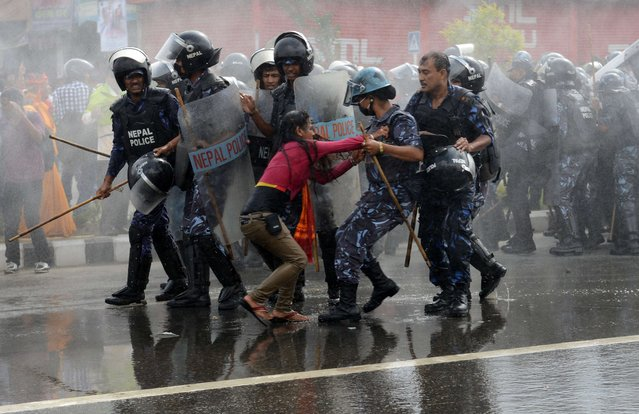 Nepalese police arrest a Hindu activist as demonstrators try to break through to a cordoned-off area near parliament during a protest demanding Nepal be declared a Hindu state in Kathmandu on September 1, 2015. Violent protests have erupted in the last few weeks in Nepal after lawmakers struck a breakthrough deal to table the draft of a new constitution, spurred by April's devastating earthquake. (Photo by Prakash Mathema/AFP Photo)