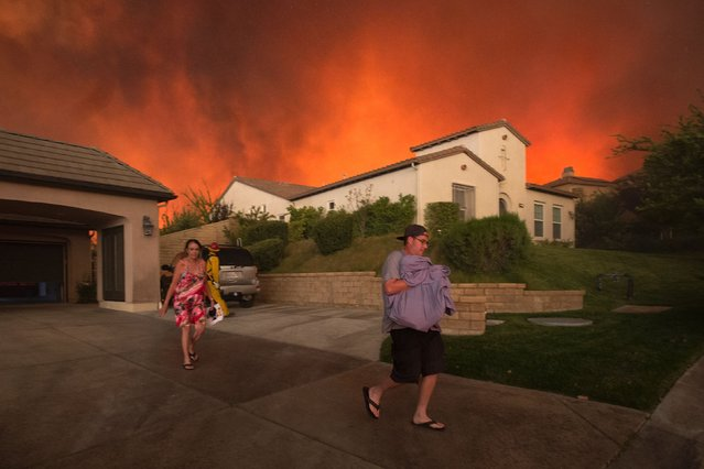 Residents flee their home as flames from the Sand Fire close in on July 23 2016 near Santa Clarita, California. (Photo by David McNew/AFP Photo)