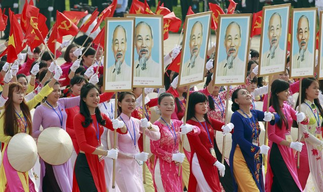 Vietnamese women, wearing traditional long dress 'ao dai', carry portraits of late Vietnamese revolutionary leader Ho Chi Minh during a parade marking their 70th National Day at Ba Dinh square in Hanoi, Vietnam September 2, 2015. (Photo by Reuters/Kham)