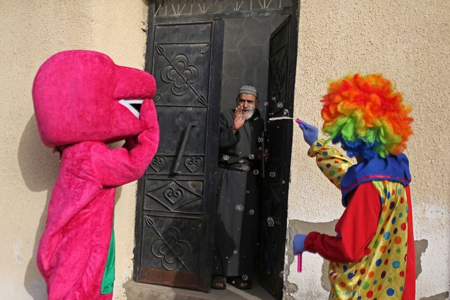 A Palestinian man waves from his home as a clown and a man in a costume perform to entertain people amid concerns about the spread of the coronavirus disease (COVID-19), in Khan Younis in the southern Gaza Strip April 19, 2020. (Photo by Ibraheem Abu Mustafa/Reuters)