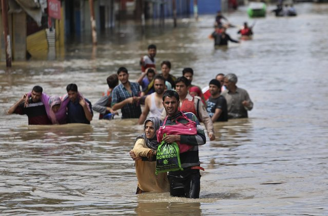 Kashmiri men evacuate women and the elderly from a flooded neighborhood in Srinagar, India, Sunday, September 7, 2014. Fast-moving floodwaters submerged large parts of the main city in Indian-controlled Kashmir on Sunday after five days of pounding rain. The flooding, the worst in 50 years, has killed at least 120 people across the Himalayan region. (Photo by Dar Yasin/AP Photo)