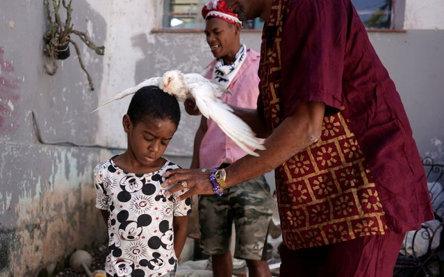 Jose Zamora, 8, has a dove rubbed over his body during the Afro-Cuban religion Santeria ceremony amid concerns about the spread of the coronavirus disease (COVID-19) outbreak, in Havana, Cuba, March 28, 2020. (Photo by Alexandre Meneghini/Reuters)