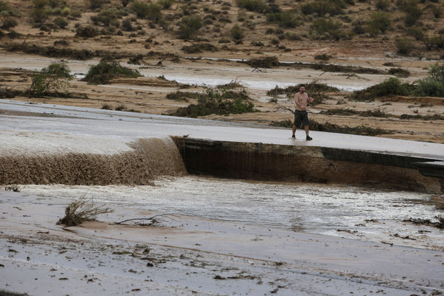Water flows down the middle of Interstate 15 in Moapa, Nev., Monday, September 8, 2014. The road is closed in both directions because of the flood damage. (Photo by John Locher/AP Photo)