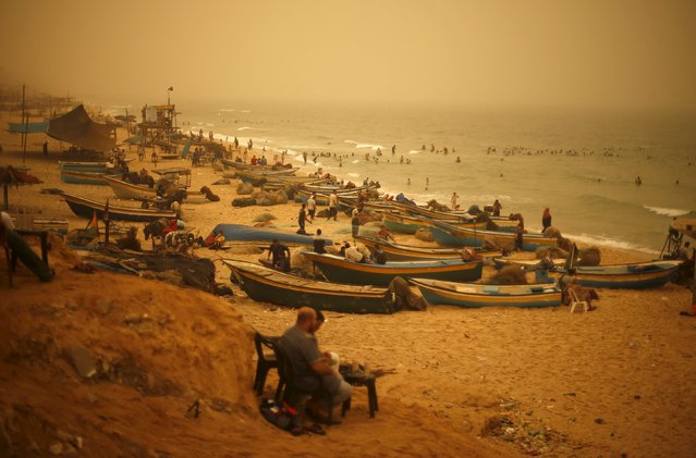 Palestinians sit on a beach along the Mediterranean Sea during a sandstorm in the northern Gaza Strip September 8, 2015. (Photo by Mohammed Salem/Reuters)