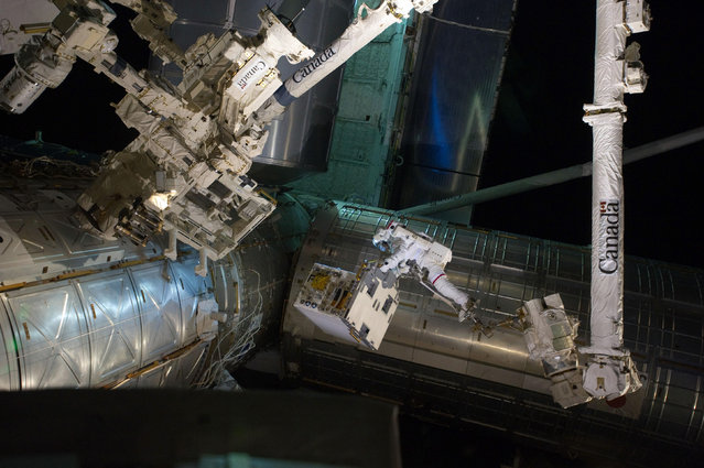 Spacewalker Ron Garan rides on the International Space Station's robotic arm  on July 12, 2011. (Photo by Reuters/NASA)
