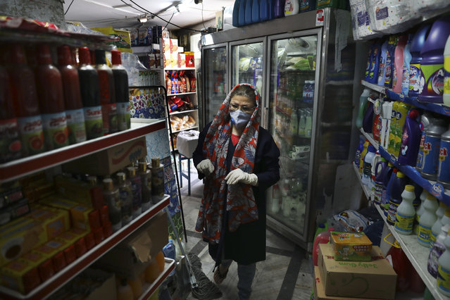 Customer Azar Arayesh, wearing a protective face mask and gloves to help prevent the spread of the coronavirus, shops in a grocery in Tehran, Iran, Tuesday, April 21, 2020. Iran is the region's epicenter of the COVID-19 pandemic, though even Iran's parliament suggests the death toll is nearly double that and overall cases remain vastly underreported. (Photo by Vahid Salemi/AP Photo)