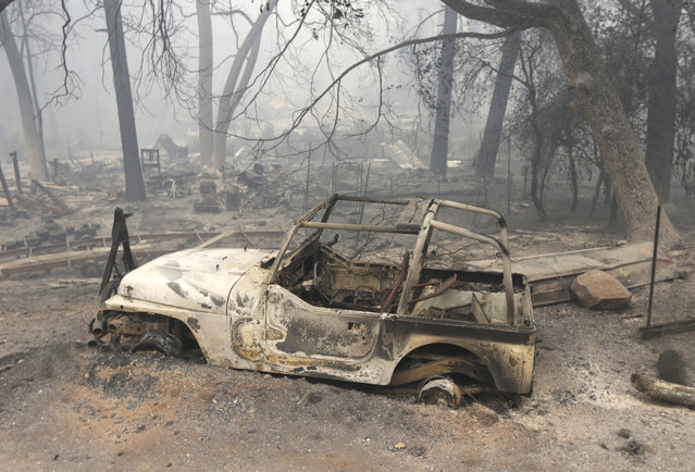 A vehicle destroyed by the Butte Fire sits on tireless rims at a home in Mountain Ranch, Calif., Saturday, September 12, 2015. Firefighters gained some ground Saturday against the explosive wildfire that incinerated buildings and chased hundreds of people from mountain communities in drought-stricken Northern California. (Photo by Rich Pedroncelli/AP Photo)
