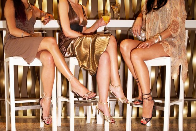 Low section of three stylishly dressed women sitting legs crossed at the bar. (Photo by sirtravelalot/Shutterstock)