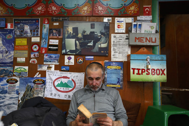 American climber Alex Goldfarb, who had to cancel his planned climb of Mount Lhotse, reads a book in Solukhumbu District May 5, 2014. (Photo by Navesh Chitrakar/Reuters)