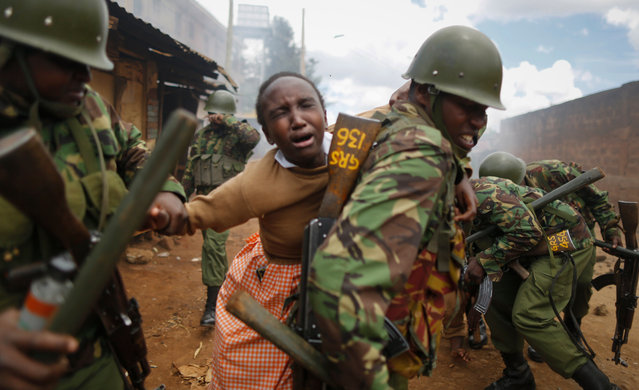 A police officer carries a school girl on his back to get her out of the scene after she was caught up in running battles with police and protesters and was affected by tear gas in Kawangware slum, Nairobi, Kenya, 30 October 2017. Kenya's education minister Fred Matiangi, who also serves as acting security minister, visited a school in Kawangware to inspect how the national exams are being conducted before he was heckled and stoned by supporters of the National Super Alliance (NASA) and its presidential candidate Raila Odinga. Tension is high in opposition strongholds of Nairobi as the country awaits for the electoral commission Independent Electoral and Boundaries Commission (IEBC) to declare President Uhuru Kenyatta the winner of the repeat presidential poll which was boycotted by Odinga. (Photo by Dai Kurokawa/EPA/EFE)