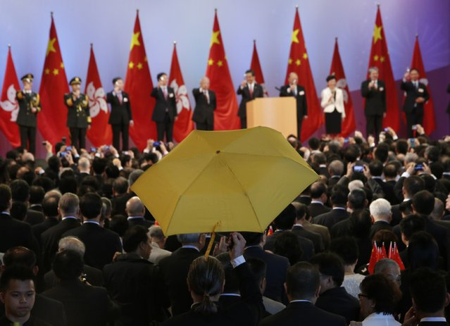 Paul Zimmerman, a district councillor, raises a yellow umbrella as Hong Kong Chief Executive Leung Chun-ying (5th R) and other officials make a toast to guests at a reception following a flag raising ceremony in Hong Kong October 1, 2014, celebrating the 65th anniversary of China National Day. As tensions subsided, weary protesters dozed or sheltered from the sun beneath umbrellas. (Photo by Bobby Yip/Reuters)
