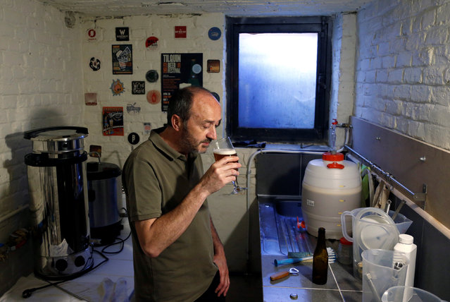 Pascal Screve, plumber and member of the Belgian Homebrewers association, inspects his own beer in the basement of his house in Brussels, Belgium, August 3, 2016. In a country where some 200 breweries produce well over 1,000 different beers, surely no one is considering brewing their own? Wrong. (Photo by Francois Lenoir/Robert-Jan Bartunek/Reuters)