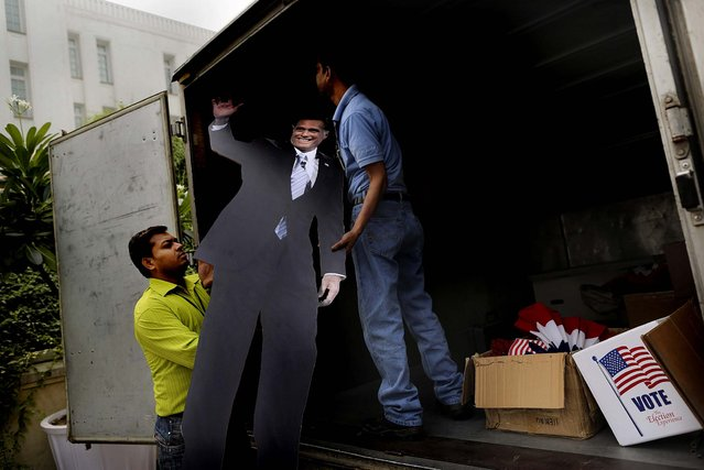 Workers from the U.S. embassy load a cardboard cutout of Republican candidate Mitt Romney into a truck after an event organized by the embassy to mark the U.S. elections, at the landmark Imperial Hotel in New Delhi, India on November 7, 2012, (Photo by Kevin Frayer/Associated Press)