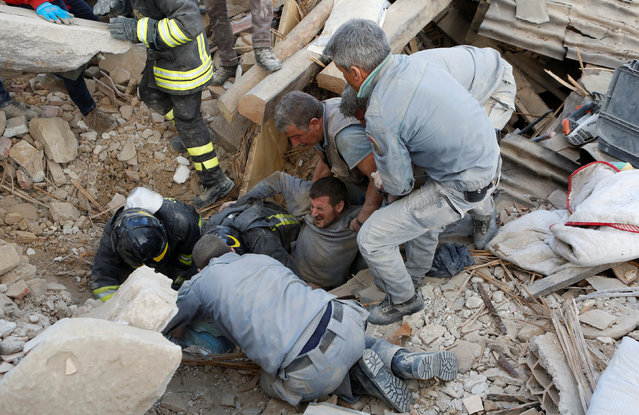 A man is rescued alive from the ruins following an earthquake in Amatrice, central Italy, August 24, 2016. (Photo by Remo Casilli/Reuters)