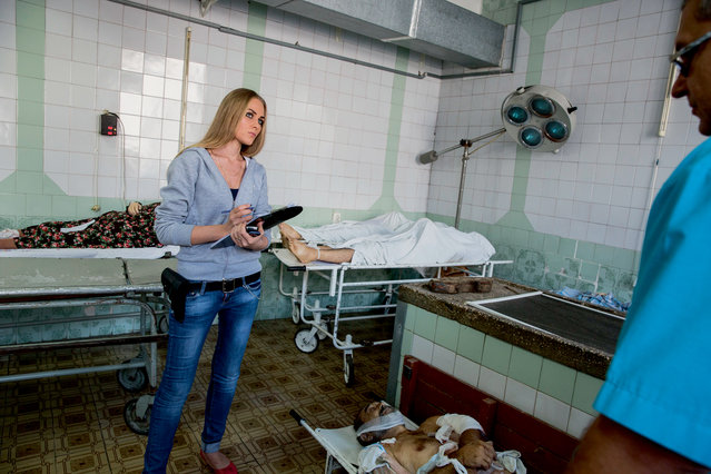 Armed pro-Russian police officer Yelena, 26, at the Donetsk mortuary on August 29, 2014. (Photo by Alvaro Canovas)