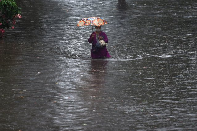 A woman walks through a flooded street after heavy rain showers in Mumbai on July 3, 2020. (Photo by Punit Paranjpe/AFP Photo)