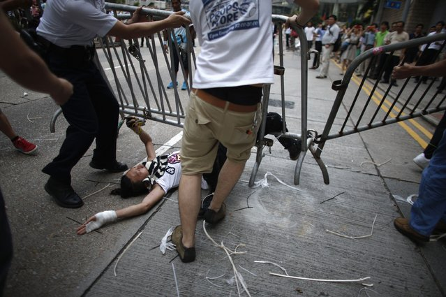 Anti-Occupy Central protesters drag a metal fence over a pro-democracy protester at the main protest site in Admiralty in Hong Kong October 13, 2014. (Photo by Carlos Barria/Reuters)
