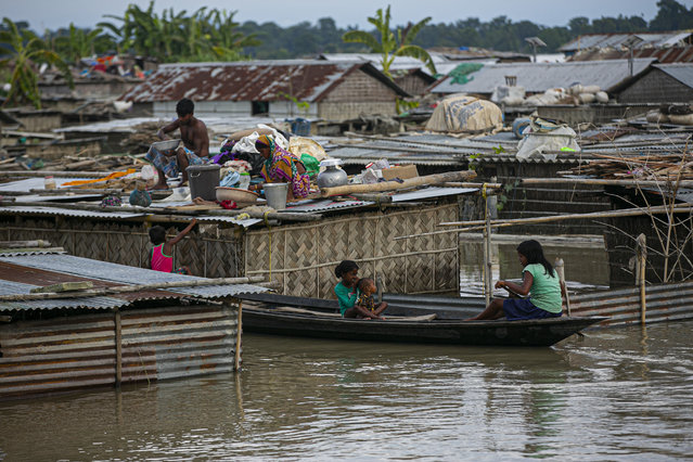 A flood affected family takes shelter on the roof of their partially submerged house along river Brahmaputra in Morigaon district, Assam, India, Thursday, July 16, 2020. (Photo by Anupam Nath/AP Photo)