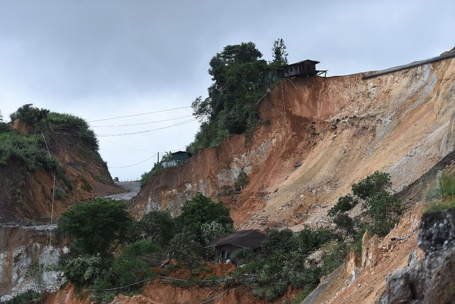 Damaged houses are seen next to the site of a deadly landslide in an area where miners work in open-cast jade mines near Hpakant in Kachin state on July 4, 2020. Dozens of jade miners have been buried in a mass grave after a landslide in northern Myanmar killed over 170, most of them migrant workers seeking their fortune in treacherous open-cast mines near the China border. (Photo by Ye Aung Thu/AFP Photo)