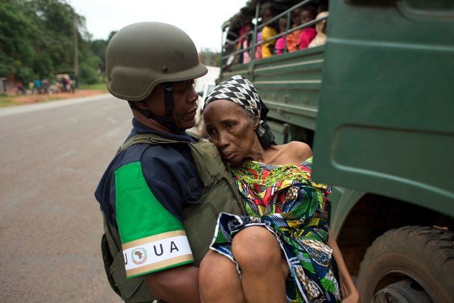 An African Union peacekeeper carries an elderly Cameroonian woman, too frail to walk, to a military vehicle shuttling Cameroonian citizens to the airport for an evacuation flight, in Bangui, Central African Republic, Friday, December 27, 2013. (Photo by Rebecca Blackwell/AP Photo)