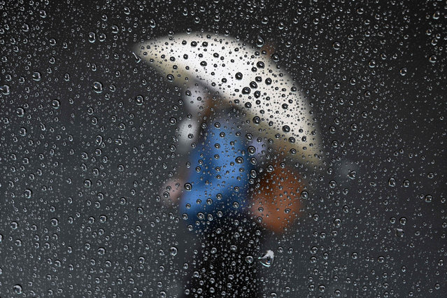 Raindrops are seen on a taxi window while a woman passes by a closed store in Buenos Aires on June 30, 2020, a day before authorities tighten virus lockdown measures against the spread of the novel coronavirus, COVID-19. The country went into lockdown on March 20 to help prevent the spread of the novel coronavirus, but those measures have been gradually eased in recent weeks. However, following a spike in coronavirus cases in the capital, a new lockdown has been imposed on the greater Buenos Aires area – home to more than a third of the country's 44 million people – from July 1-17. (Photo by Juan Mabromata/AFP Photo)