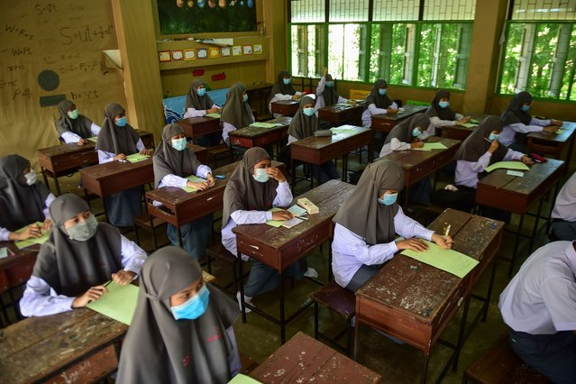 Muslim students wearing face masks attend a class at the Attarkiah Islamic School in the southern Thai province of Narathiwat on July 2, 2020, as schools across Thailand reopened after being temporarily closed to concerns about the COVID-19 novel coronavirus. (Photo by Madaree Tohlala/AFP Photo)
