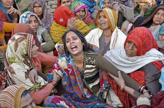 Dharamvati (C), wife of Indian soldier Hemraj Singh, weeps outside her house before Singh's body was brought for cremation in the Mathura district of the northern Indian state of Uttar Pradesh January 9, 2013. India denounced Pakistan on Wednesday over a firefight in the disputed territory of Kashmir in which two Indian soldiers were killed, but the nuclear-armed rivals both appeared determined to prevent the clash escalating into a full diplomatic crisis. (Photo by Reuters/Stringer)