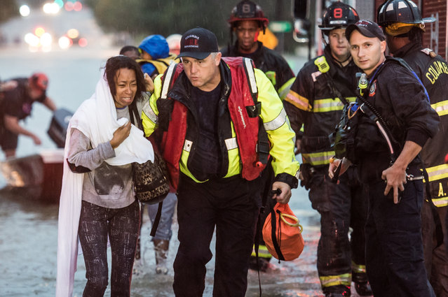 Charlene Stennis is escorted to safety after her son was rescued from a stranded vehicle in a flooded roadway October 4, 2015 in Columbia, South Carolina. South Carolina experiencied a record rainfall, with at leasrt 11.5 inches falling October 3. (Photo by Sean Rayford/Getty Images)