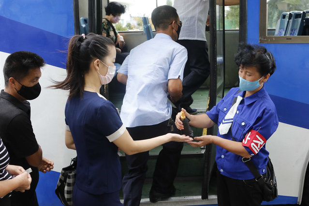 A passenger wearing a face mask to help curb the spread of the coronavirus is disinfected her hand before getting on a trolley bus in Pyongyang, North Korea, Thursday, August 13, 2020. (Photo by Jon Chol Jin/AP Photo)