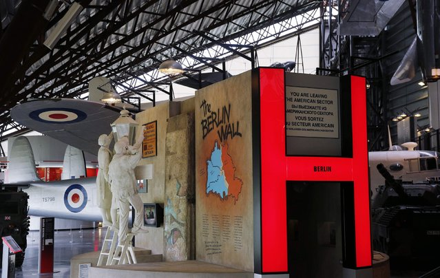 A section of the Berlin Wall is surrounded by a display in the Cold War exhibition at the Royal Air Force Museum in Cosford, England, October 14, 2014. (Photo by Suzanne Plunkett/Reuters)