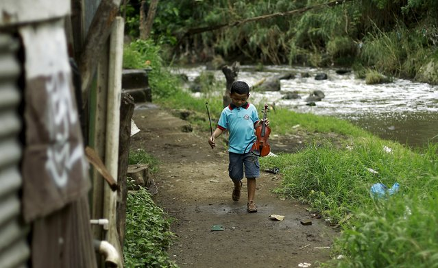 Ruben Escoriano, 6, walks outside his house before his fiddle lesson at the Integral System of Artistic Education for Social Inclusion SIFAIS center in the poor neighborhood of La Carpio, Costa Rica October 8, 2015. (Photo by Juan Carlos Ulate/Reuters)