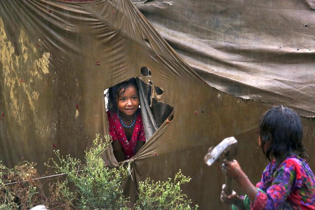 A nomadic girl talks to her sister from a hole in a ripped tent during rainfall at a slum in Peshawar, Pakistan, Tuesday, September 1, 2020. (Photo by Muhammad Sajjad/AP Photo)
