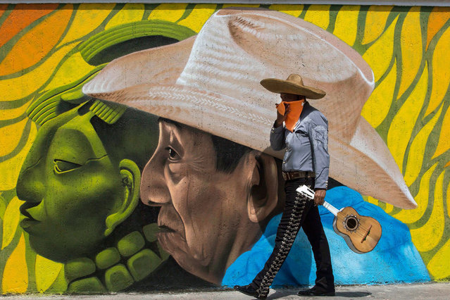A Mariachi walks past a grafitti in Merida, state of Yucatan, Mexico on August 15, 2020 amid the COVID-19 coronavirus pandemic. (Photo by Hugo Borges/AFP Photo)