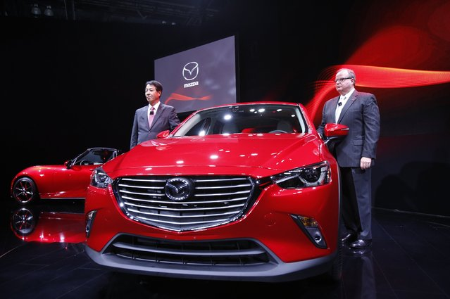 President and CEO of the Mazda Motor Corporation Masamichi Kogai (L) and Mazda North America President James O'Sullivan pose next to the Mazda CX-3 Compact Crossover Utility vehicle during the model's world debut at the Los Angeles Auto Show in Los Angeles, California November 19, 2014. (Photo by Mario Anzuoni/Reuters)