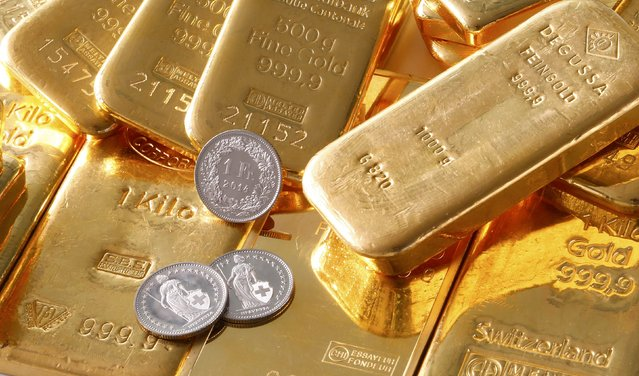 """Gold bars from the vault of a bank and Swiss one franc coins are seen in this illustration picture taken in Zurich November 20, 2014. The """"Save our Swiss gold"""" proposal, spearheaded by the right-wing Swiss People's Party (SVP), aims to ban the central bank from offloading its reserves and oblige it to hold at least 20 percent of its assets in gold. The referendum is scheduled for November 30. The SVP argues it would secure a stable Swiss franc. (Photo by Arnd Wiegmann/Reuters)"""